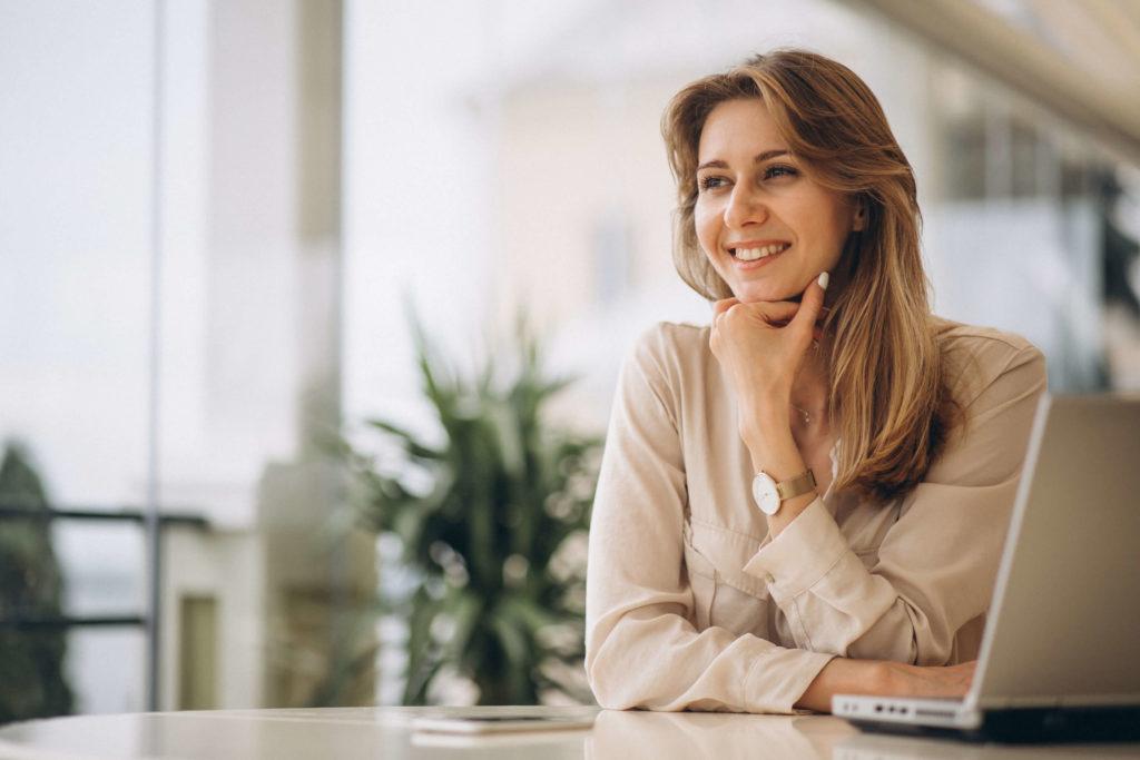 Mulher feliz sentada em uma mesa em um lugar claro, com os braços apoiados em uma mesa onde está um notebook