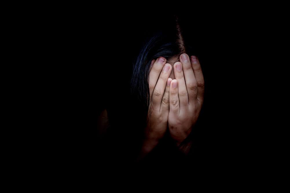 Fundo preto com uma pessoa com as mãos no rosto com medo