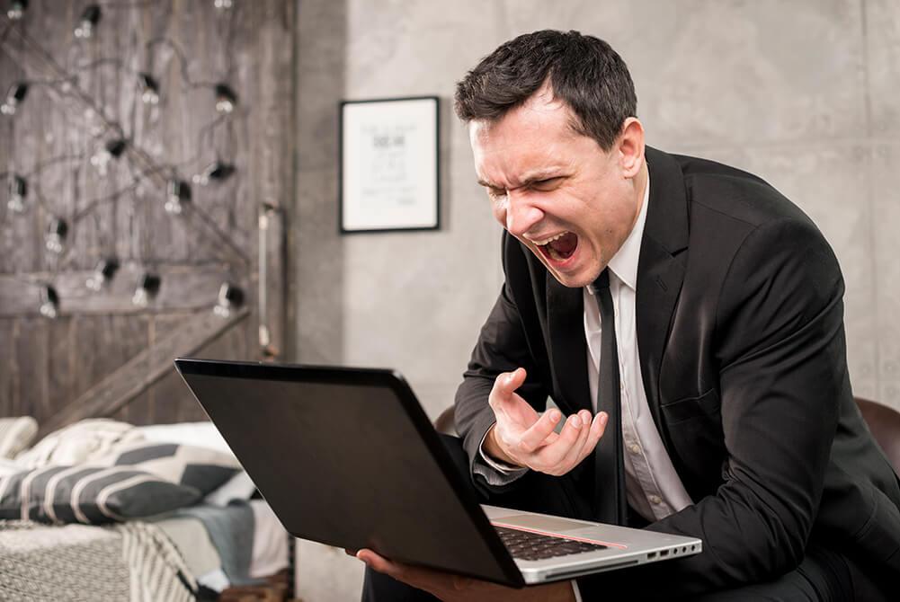 Homem com raiva gritando para o notebook que segura nas mãos