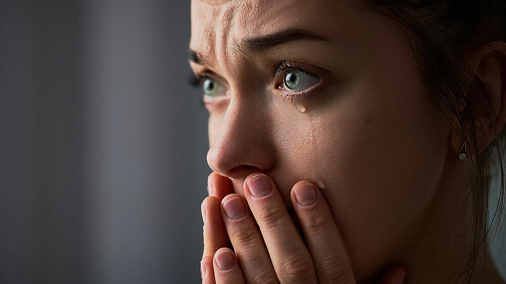 Mulher com expressão triste com as mãos no rosto em frente aos lábios , com uma lágrima escorrendo pelo rosto