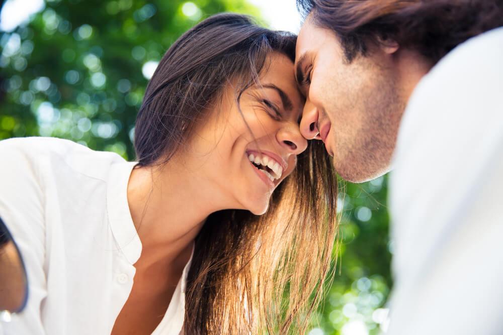homem e mulher formando um casal feliz e sorrindo, com ambas as testas encostadas com uma árvore ao fundo