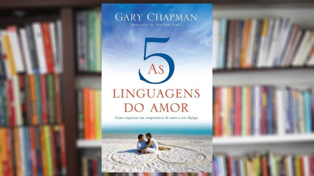 Foto do livro As 5 Linguagens do Amor com fundo desfocado de uma prateleira de livros