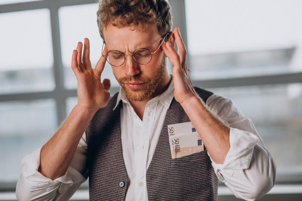 Homem loiro de óculos com notas de 50 no bolso do colete e com as mãos na cabeça com expressão de dor