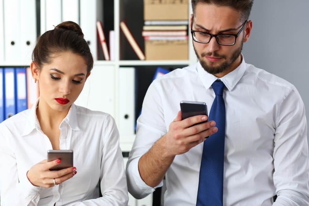 homem e mulher vestido de maneira mais formal olhando para os celulares em suas mãos