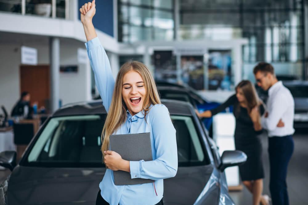 mulher vendedora de carros comemorando o sucesso nas vendas, com casal de clientes ao fundo ao lado do carro comprado