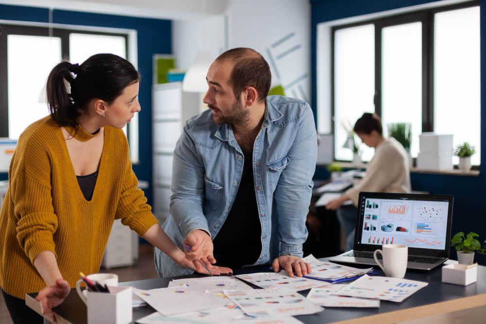 homem e mulher em frente a uma mesa com relatórios do negócio conversando sobre os resultados