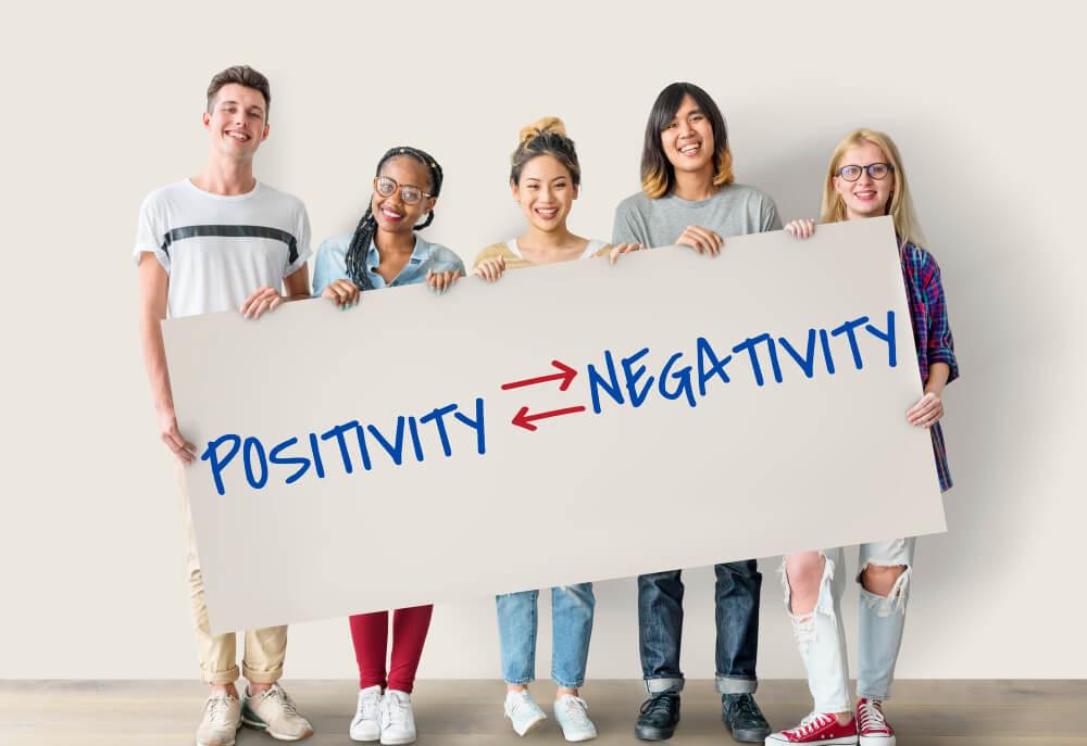Cinco pessoas sorrindo e segurando uma placa com setas apontando para palavras positividade e negatividade, escritas em inglês posititivity, negativity.