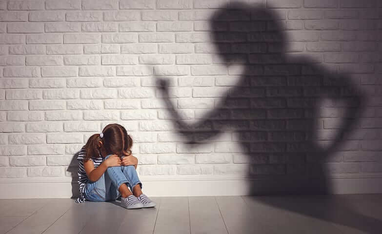 Criança acuada sentada no chão com a cabeça entre os joelhos. Abraçando os joelhos. Em frente à uma parede de tijolos brancos. Sombra de uma mulher na parede apontando o dedo para a menina.