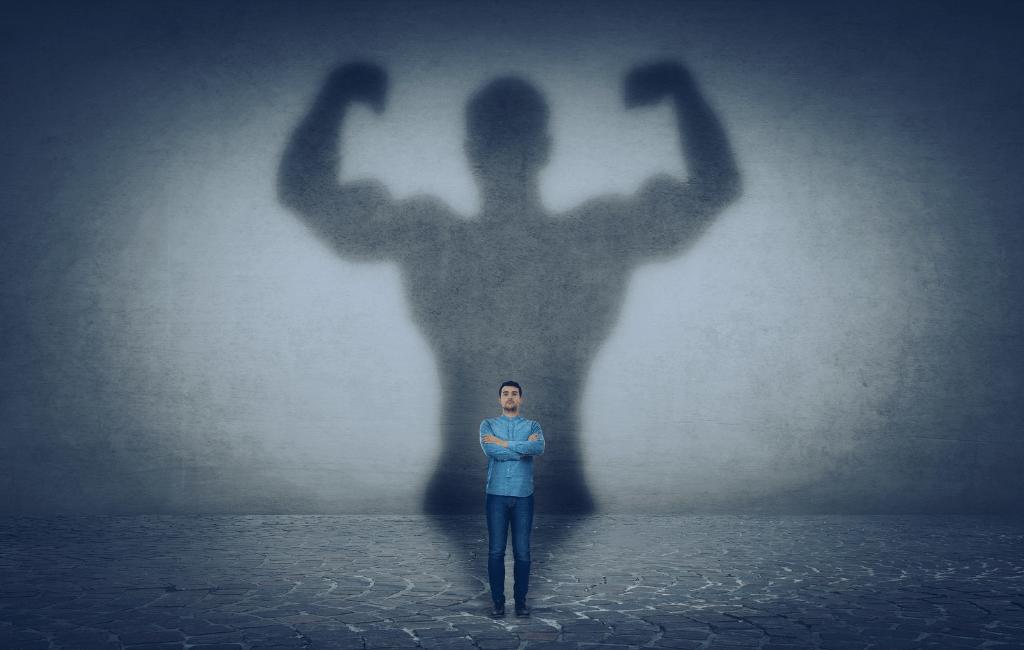homem de braços cruzados com sombra de homem forte mostrando músculos dos braços
