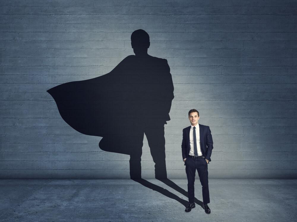Homem jovem de terno em um local com parede e chão de cimento, com sua sombra marcando na parede como um super-herói