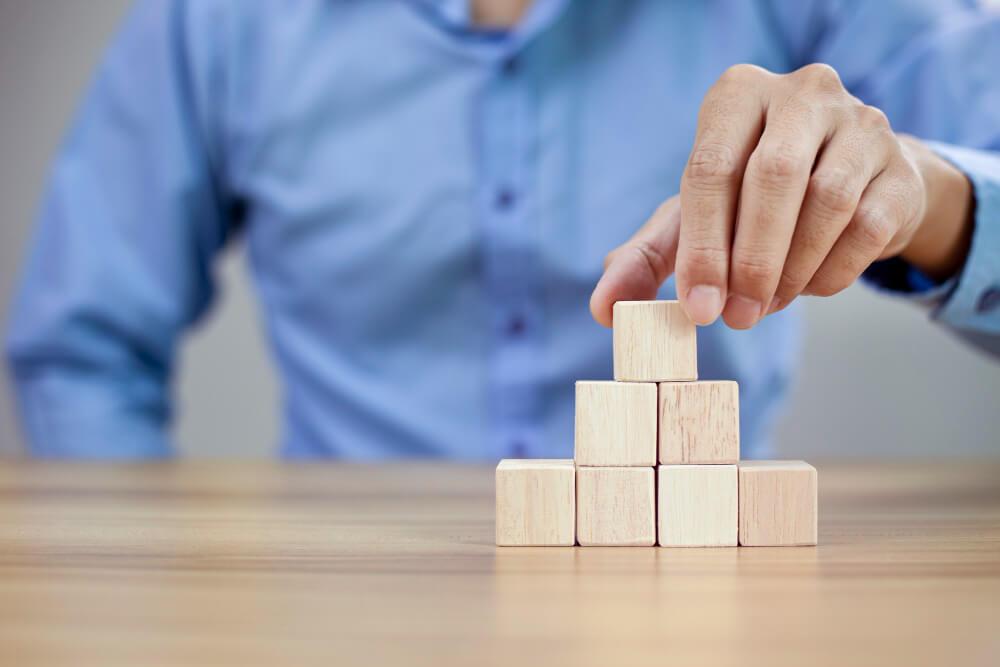 Homem de camisa social azul, fazendo uma pirâmide com pequenos blocos de madeira em cima da mesa.