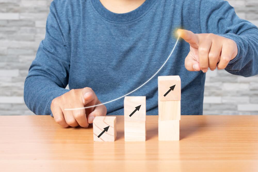Homem de camisa azul sentado em frente à mesa, com blocos de madeira em formato de gráfico crescente em cima da mesa e homem apontando com o dedo fazendo uma curva de crescimento no ar, apontando para os blocos.