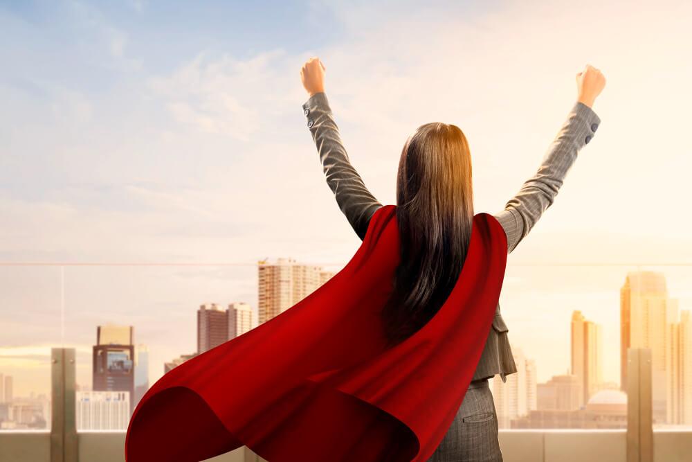 Mulher de costas com as mãos para o alto e vestida de terninho cinza com uma capa vermelha de super heroína