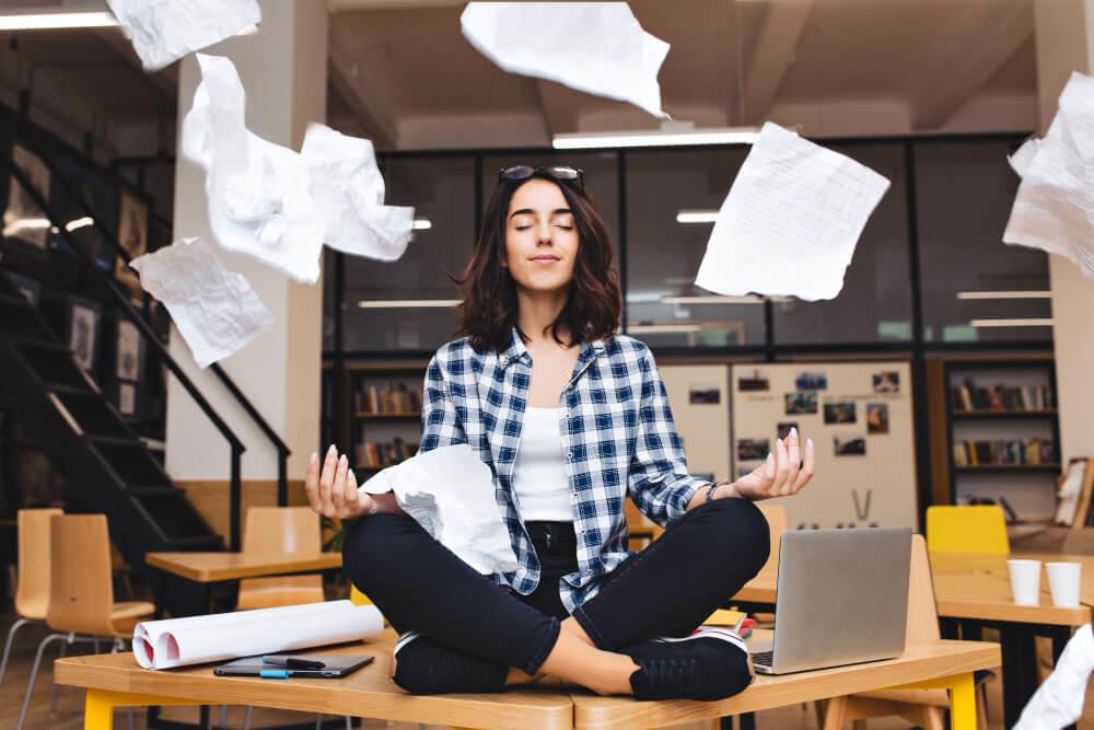 Mulher sentada na mesa do escritório meditando enquanto os papéis voam em torno dela