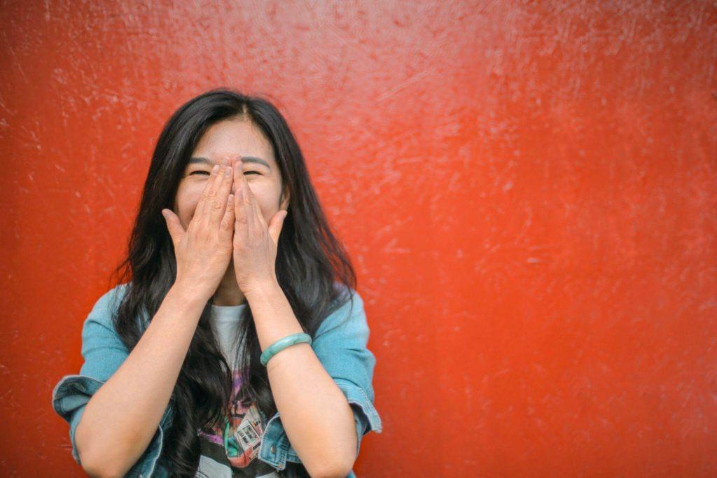 Moça asiática com as mãos unidas na frente do rosto cobrindo a boca e nariz com expressão de alegria, em frente a uma parede vermelha