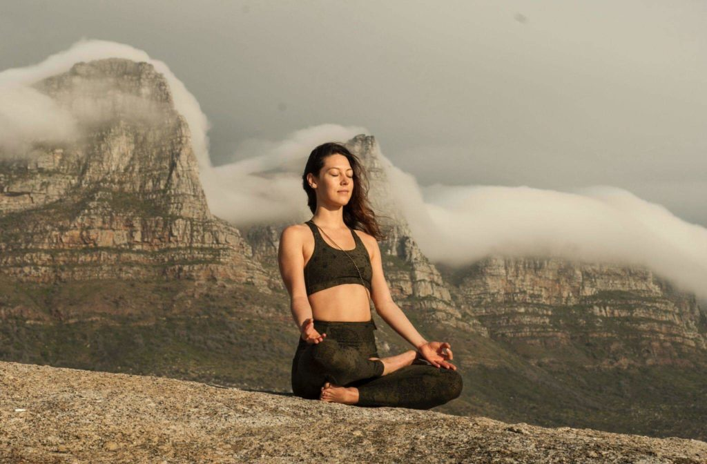 Mulher meditando no alto de uma montanha