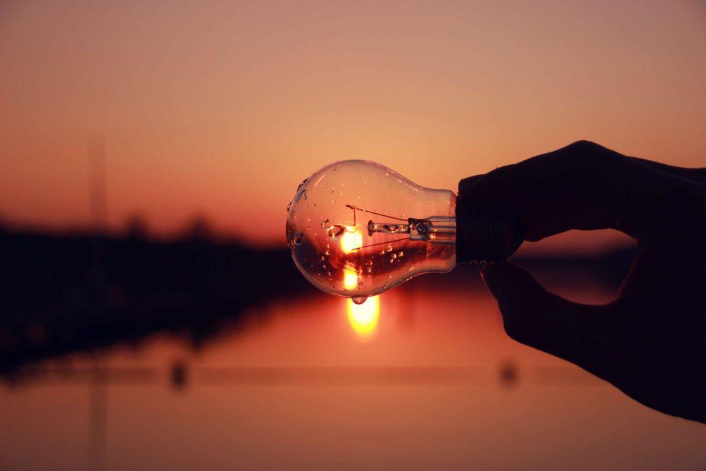 Mão segurando uma lâmpada deitada com a luz representada pelo sol no horizonte do céu avermelhado atrás