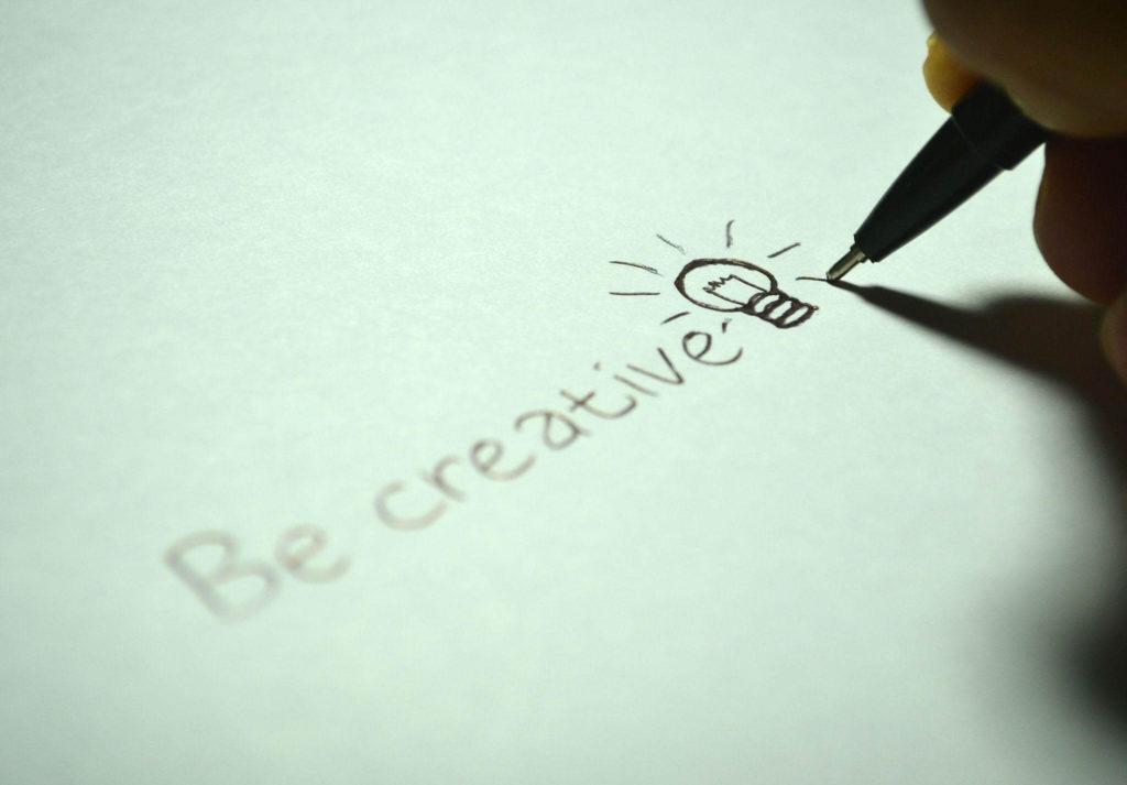 Alguém escrevendo em um papel a frase Be Creative e uma lâmpada no final